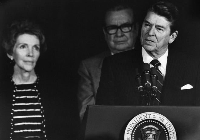 NOVEMBER 30, 1981: President Ronald Reagan speaks at a fund-raising cocktail party in Cincinnati Monday, 11/30/81, with his wife, Nancy, left, and Ohio Governor James A. Rhodes, who introduced Reagan to the crowd. The party was one of two events the Reagans attended during a short stop in the city while enroute home from a Thanksgiving break in California.