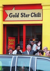Text: 1998.0917.06.01 CLINTON President Bill Clinton leaves a Gold Star Chili parlor on Race St. in Over-the-Rhine. Clinton visited Cincinnati to attend a fund raiser at the home of Stan Chesley and then toured a portion of Over-the-Rhine.