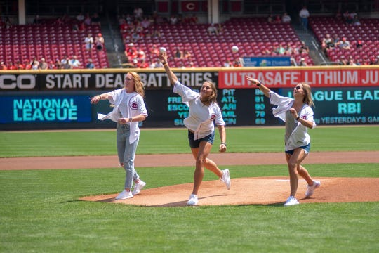 Washington Spirit players from left, Tori Huster, Aubrey Bledsoe and Bayley Feist, throw out the ceremonial first pitch before a Cincinnati Reds game on July 28, 2019, at Great American Ball Park.