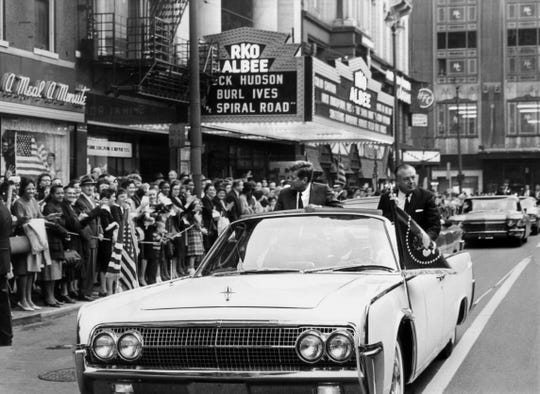 "OCTOBER 5, 1962: John F. Kennedy, Fifth Street, downtown, Cincinnati. John F. Kennedy, 35th president of the United States, rides down Fifth Street on a warm Friday afternoon. At his side in the open limousine is Ohio's governor, Michael V. DiSalle. The president was in Cincinnati to stump for local candidates. He stayed just long enough to give a  10-minute speech from a platform by Fountain Square. Behind the platform, a woman muttered: I'm going to shoot the president."" As three police officers grabbed her, she hit one in the face with her ""weapon"" - a camera."
