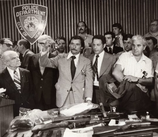 "New York City Police Detective Edward Zigo displays the .44 caliber gun believed use by David Berkowitz as the ""Son of Sam.""  Mayor Abraham Beame, far left, and numerous police officials attended the press conference Aug. 11, 1977 where the arrest of Berkowitz in connection with a number of shootings was announced."