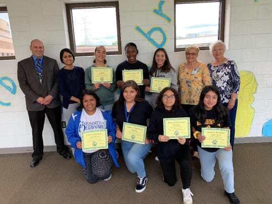 North Brunswick High School Principal Michael Kneller, (left to right), Creative Wrting Teacher Nimishi Patel, Kayla Harris, Seairah Chiles, Trinity Solano, North Brunswick Woman's Club Performing Arts Chairperson Susan Kneller, NBWC President Joyce Dreger, Picture kneeling are Naomi Silva-Valencia, (left to right), Mayely Munoz, Adrianna Casas, and Stephanie Miranda. Not pictured is Olivia Baldwin.