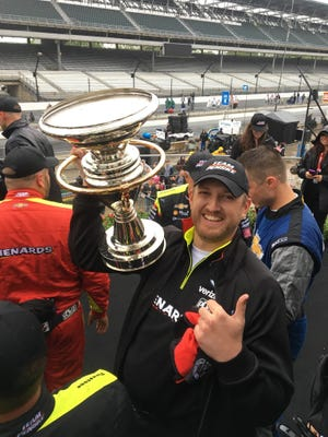 Colin Davis of West Lafayette with the trophy Team Penske claimed for winning the Indy Grand Prix, a precursor to the Indianapolis 500. Davis joined Team Penske in May.