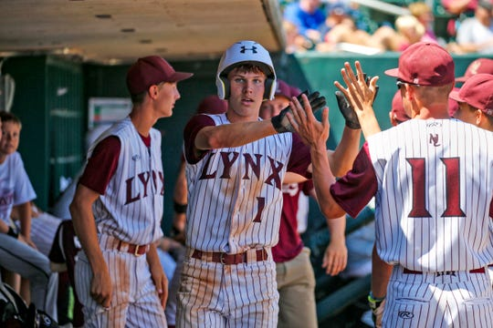 Jake Hilmer of North Linn high fives teammates in the dugout during the state semifinal game against  Monday, July 29, 2019.