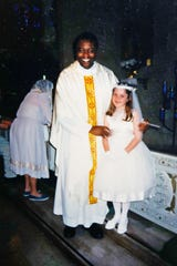 This undated photo provided by Mary Rose Maher in 2019 shows her as a child standing with Rev. Komlan Dem Houndjame at The Assumption of the Blessed Virgin Mary Church in Detroit. Two years after arriving at The Assumption of the Blessed Virgin Mary Church in 1999, Detroit Archdiocese officials said they asked Houndjame to return to his home country, Togo, after learning of accusations of sexual misconduct against him in Detroit and at an earlier posting in Florida. Instead he went to a treatment facility in St. Louis. In 2002, Detroit police arrested him and charged him with sexually assaulting a member of the church's choir.