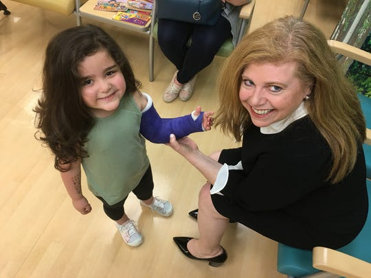 Willow Mullins, 4, of Monroe, poses for a photo as Children's Hospital of Michigan CEO Luanne Thomas Ewald signs her waterproof cast during at check up at the clinic on May 30, 2019.