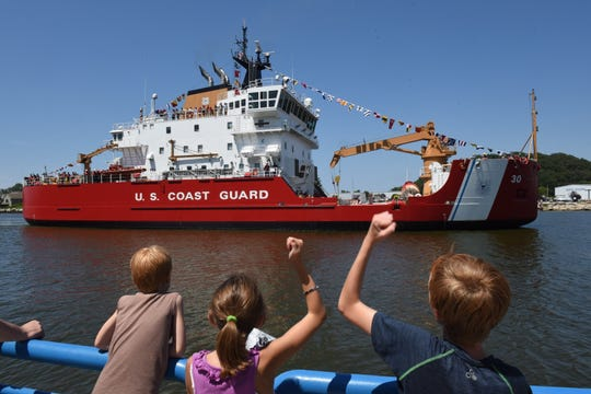 From left to right, Case Bultman, 7, Leah Bultman, 8, and Luke Bultman, 11, watch and raise their fists signaling for U.S. Coast Guard Mackinaw (WLBB-30) to blow its horn as it makes its way through the Grand Haven Channel along with other Coast Guard ships arrivals as part of the annual Grand Haven Coast Guard Festival at Escanaba Park in Grand Haven, Mich. on Monday, July 31, 2017.