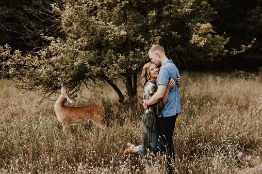 A deer in Saugatuck Dunes State Park eats a tree behind Dori Anne and Austin Swiercz. The couple's July 23, 2019 engagement photo session got interrupted by the photobomber.