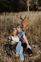 A deer in Saugatuck Dunes State Park approaches behind Dori Anne and Austin Swiercz. The couple's July 23, 2019 engagement photo shoot was interrupted by the wild photobomber.