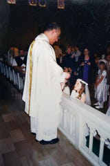 This undated photo provided by Mary Rose Maher shows her as a child during her First Dommunion with Father Eduard Perrone at The Assumption of the Blessed Virgin Mary Church in Detroit.