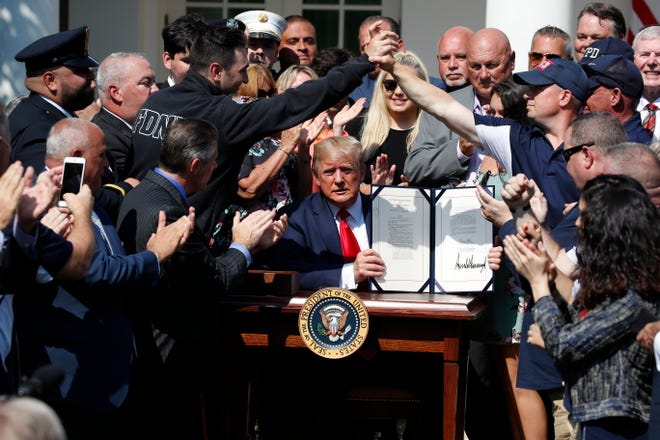 President Donald Trump holds up the signed H.R. 1327 bill, an act ensuring that a victims' compensation fund related to the Sept. 11 attacks never runs out of money, in the Rose Garden of the White House, Monday, July 29, 2019, in Washington.