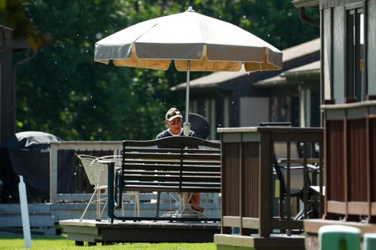 Father Eduard Perrone reads under an umbrella in Warren, Mich., Friday, June 7, 2019.