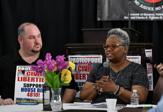 State Rep. Isaac Robinson, left, listens while Tawana Petty of Detroit Community Technology Project speaks at a town hall meeting discussing the use of facial recognition software by law enforcement.