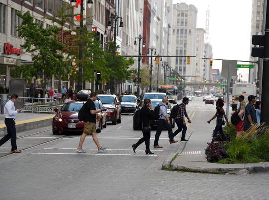 Pedestrians cross a revitalized Woodward Avenue in downtown Detroit.
