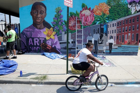 A boy rides his bicycle Monday after volunteering to paint a mural outside the New Song Community Church in the Sandtown section of Baltimore.