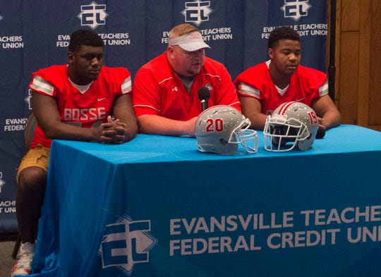 Bosse's Head Coach Eric Schnur, center, answers questions about the upcoming seasons with Elijah Harris, left, and Shay Mcrath, right, during High School Football Media Day 2019 Monday, July 29, 2019.