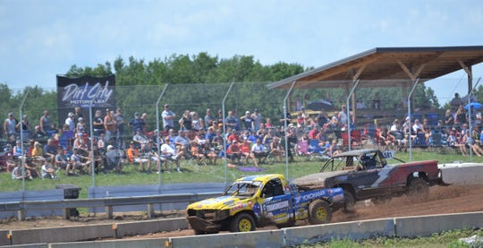 Racers pass the start-finish line in the mod carts division Sunday in the Dirt City Duel off-road races at Lena.