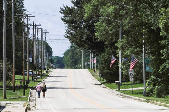 People walk down state highway 156 through the center of Navarino, Wis., Monday, July 29, 2019.