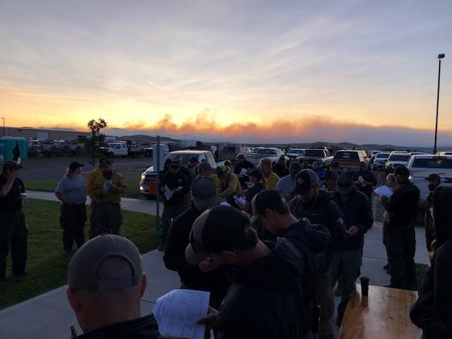 Plumes of smoke are visible from the North Hills Fire Sunday during a fire briefing.