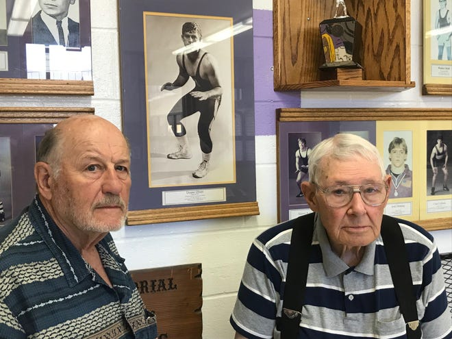 Retired Big Sandy wrestling coach Ron Mangold and Pioneer wrestling historian Bernie Ellingson flank Duane Olson's portrait on the Duane Olson Memorial Wall of Champions inside the entrance to the Big Sandy High School gym.