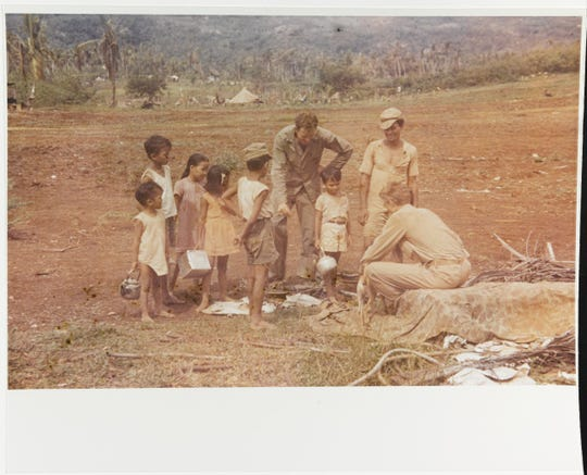 Marines talking with a group of local children on Guam in August 1944. Note tent encampment in the background.