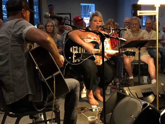 "Singer-songwriter Leslie Satcher (center) on Saturday night performs a song, ""Every Day Counts,"" that she had written just hours earlier at the Henderson County home of Joel Hopper. It's believed to be a first for the Sandy Lee Watkins Songwriters Festival."
