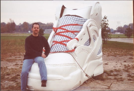 Jerome Pohlen takes a seat on the really big sneaker at the Steve Alford All-American Inn.