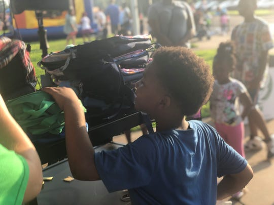 Students excitedly picked out backpacks of school supplies if their names were pulled in a drawing during a back-to-school block party at Isaac Lane Elementary.