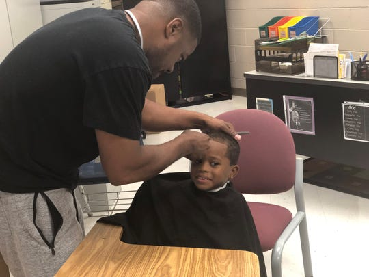 Frank Jordan-Chalupa, a second grader at Isaac Lane, gets a free haircut during the school's back-to-school bash Friday.