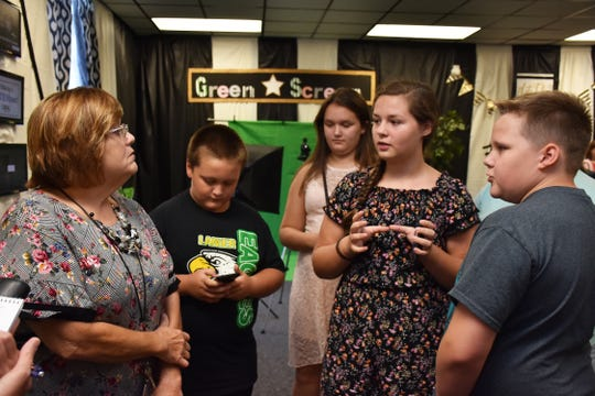 Renee Powell, left, and former STEM Scouts discuss creating a video to welcome students for the new school year.