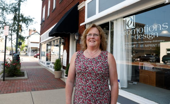 Katherine Cheek stands outside of her business Promotions by Design Monday morning, July 29, 2019, on Columbus Street in downtown Lancaster. Cheek recently decreased the footprint of the business to a smaller space which caused a chain reaction with Sparkle & Rust and the Visit Fairfield County moving into newly opened spaces in the building at the corner of North Columbus and West Wheeling streets.