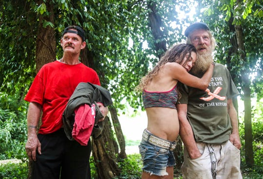 Amanda Bradshaw hugs boyfriend David Walston as they watch along with friend Gary Reed the home the couple built out of discarded lumber and pallets gets demolished Monday afternoon. The trio with three others were living in the woods along the banks of Silver Creek in New Albany before the city ordered the camp to be removed. July 29, 2019