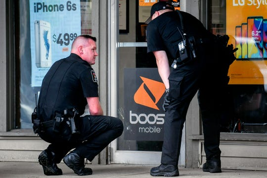Lansing Township Police inspect a bullet hole in the door at the scene of a shooting that left one man with non-life-threatening injuries on Monday, July 29, 2019, at the Boost Mobile shop on South Waverly Road in Lansing Township.