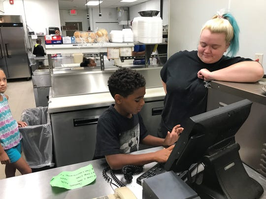 P.J. Miller types in his pizza order under the guidance of a Gionino's employee Monday. P.J. has participated in the UMADAOP Summer Camp.