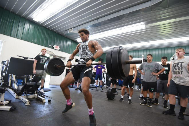 Elijah Hughes lifts last week in the weight room at Clear Fork High School.