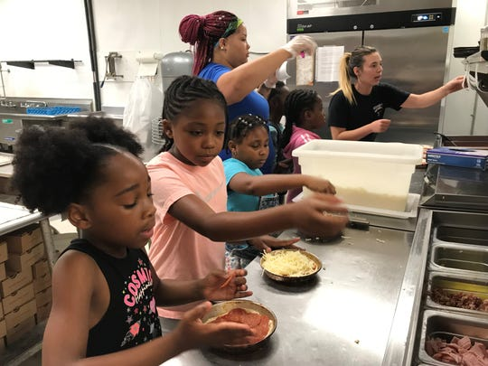 Tiphani Jackson, 8,  at left, Jaylin Luttrell, 7, and Kamani Phillips, 8, learned to make their own pizzas Monday at Gionino's Pizzeria on West Fourth Street during the UMADAOP Summer Camp as employees of the business help them with their orders.