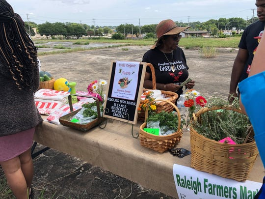 Local vendors sell items during an event unveiling plans for a farmers market and community center in Raleigh.