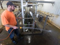 Peter Thewis washes down the milking parlor after 110 cows were milked Wednesday, July 24, 2019 on their family's farm in Mellen, Wis. Cleanliness is a priority for diary farmers because their milk is consistently tested for quality. Thewis says they spend two-man hours a day cleaning the parlor, not counting additional times where they do a more extensive cleaning.