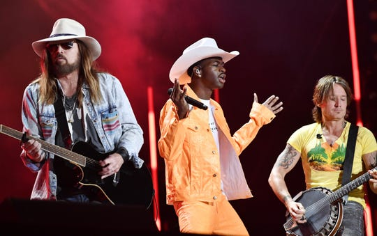"Billy Ray Cyrus, left, Lil Nas X and Keith Urban performs the huge hit, ""Old Town Road,"" during the CMA Music Fest June 8, 2019 at Nissan Stadium."