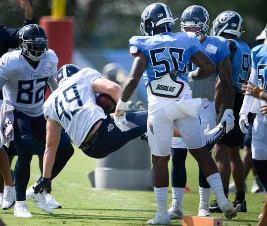 Titans tight end Parker Hesse (49) is dropped to the ground by linebacker Derick Roberson (50) during practice at Saint Thomas Sports Park Monday, July 29, 2019, in Nashville, Tenn.