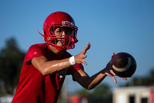 Immokalee High School quarterback Lukas Soto takes a snap during practice, Monday, July 30, 2019, at Immokalee High School.