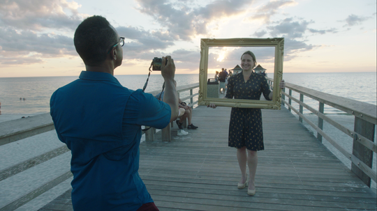 """Family Pictures USA"" producer Thomas Allen Harris snaps a photo of Caroline Ridgway on the Naples Pier."