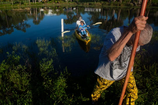 From right to left, Stan Chrzanowski, a volunteer for Florida Lakewatch, helps Kamila Perez and Duke Vasey launch a kayak for water sampling at a pond by Collier Boulevard on Friday, July 19, 2019, in Golden Gate Estates. Florida Lakewatch is a citizen volunteer lake monitoring program that facilitates citizen participation in the management of Florida lakes, rivers and coastal sites through monthly monitoring activities.