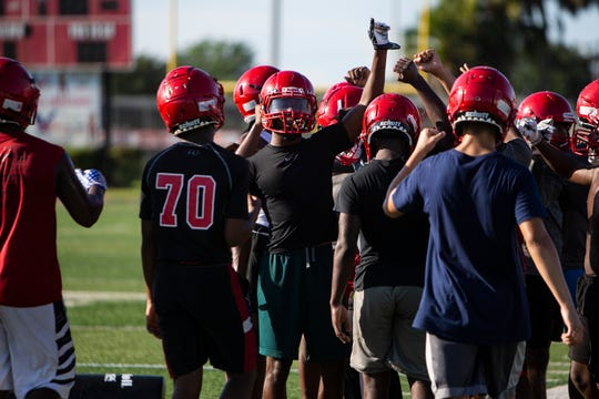 Immokalee football team huddle around Charles Toombs third from left, before football practice, Monday, July 30, 2019, at Immokalee High School.