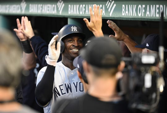 Yankees shortstop Didi Gregorius (18) is greeted in the dugout after hitting a tow run home run during the fourth inning against the Boston Red Sox at Fenway Park.
