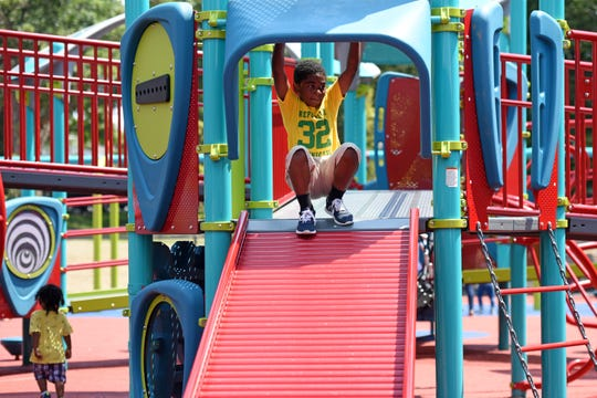 A new all-access playground opened at Watsessing Park in Bloomfield, built to allow special needs children to play alongside all of their friends. Christian Henry, 5, of Bloomfield, prepares to slide down a wide slide in the playground.