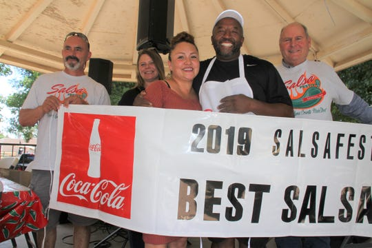 Torre Johnson and wife Bella show off their 2019 Salsa fest banner.