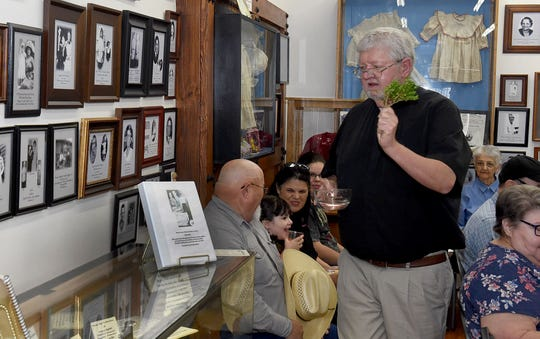 The Rev. Russell Harrington, St.Landry Catholic Church pastor, bestows a blessing onto the artifacts and photos on display a the Opelousas Orphan Train Museum where the annual Orphan Train Reunion was held Saturday.