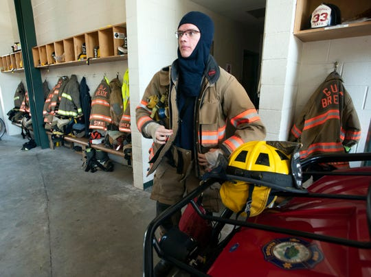 Carl Hoffman, a volunteer firefighter with the Gulf Breeze Fire Department, changes into his bunker gear to respond to a call Monday.