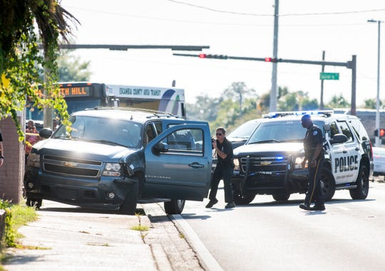 Pensacola police investigate the scene of a crash near Cervantes and D streets on Monday. Authorities say the driver of a Chevrolet Suburban was involved in several hit-and-run crashes and then rammed an officer's patrol car, leading the officer to fire shots at the vehicle.